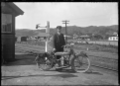J McDonald standing beside a Douglas motorcycle, on the platform of the old Silverstream Railway Station, circa 1921. ATLIB 288145.png
