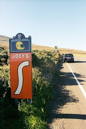 26th Milestone, Isle of Man - The parked car (the photographer's?) is obscuring the view of Joey's bend