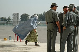 Woman passing next to police in Kabul