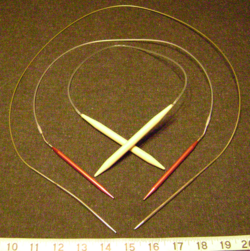 Circular knitting needles in three different lengths and sizes.  The tips of the outermost, longest one is US size 5 and chrome-plated for speed, whereas the innermost tips are wood and US size 15; the middle red metal tips are US size 9.