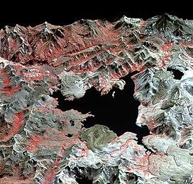 A false colour satellite image of Laguna del Maule, a lake with an irregular shape within mountains