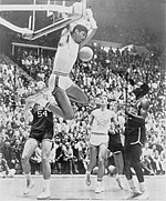 A young black man is completing a two-handed reverse slam dunk during a college basketball game. The photograph is in black and white.