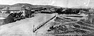 "Pueblo de Los Ángeles - La Plaza, as seen from the Pico House, c.1869. The ""Old Plaza Church"" is to the left, the brick reservoir on the right, and in the center of the plaza, was the original terminus of the Zanja Madre."
