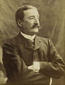 Fotografia em preto e branco de um homem de bigode em pé com os braços cruzados.