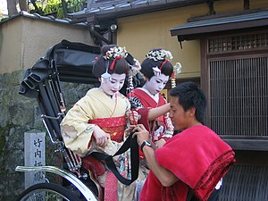 Pulled rickshaw - Tourists dressed as maiko on a rickshaw in Kyoto, Japan