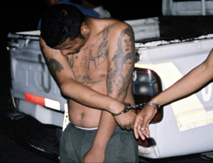 Crime in El Salvador - An MS-13 suspect bearing gang tattoos is handcuffed.