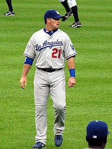 A Caucasian male wearing a baseball uniform with the number 21 and the word Los Angeles in cursive is walking forward and looking to his right.
