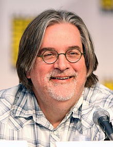 A smiling man in glasses and a plaid shirt sits in front of a microphone.