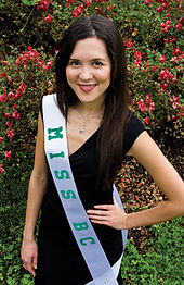 A photograph of a woman looking at the viewer and smiling while wearing a black dress, an necklace, and a white sash with green letters on it