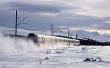 A four-car multiple unit running across a snow-covered plain with mountains in the background