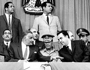 1969 Libyan coup d'état - Gaddafi at an Arab summit in Libya, shortly after the September Revolution that toppled King Idris. Gaddafi sits in military uniform in the middle, surrounded by President Gamal Abdel Nasser (left) and Syrian President Nureddin al-Atassi (right)