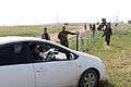 Nepalese soldiers with the Birendra Peace Operation Training Center guide a role player's vehicle to a search area at the vehicle checkpoint training lane during Khaan Quest 2013 at Five Hills Training 130807-M-DR618-068.jpg