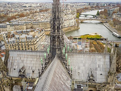 View of roof with transepts and base of spire and 16 statues of apostels and evangelists of Notre-Dame de Paris in France.