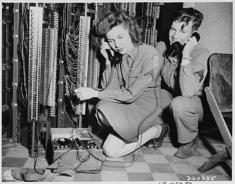PFC Gladys Bellon, Basile, Louisiana, one of the 27 WAC switchboard operators flown from Paris for the Potsdam Conference and Sgt. Robert Scott of Pittsburgh, Pennsylvania, test lines in the frame room of the Victory switchboard at U. S. headquarters at Babelsburg, Germany.