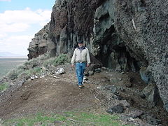 Photograph of a man walking at the base of a cliff