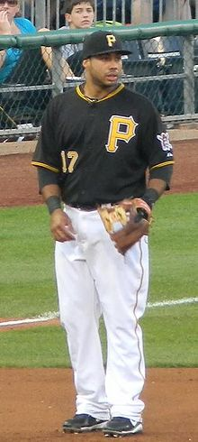 "A man in a black baseball uniform and cap with yellow ""P""s on his cap and chest with a baseball glove on his left hand."