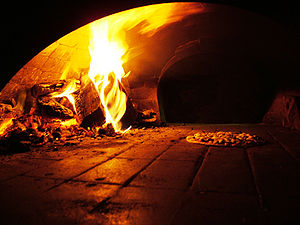 A wood-burning pizza oven baking a pizza.