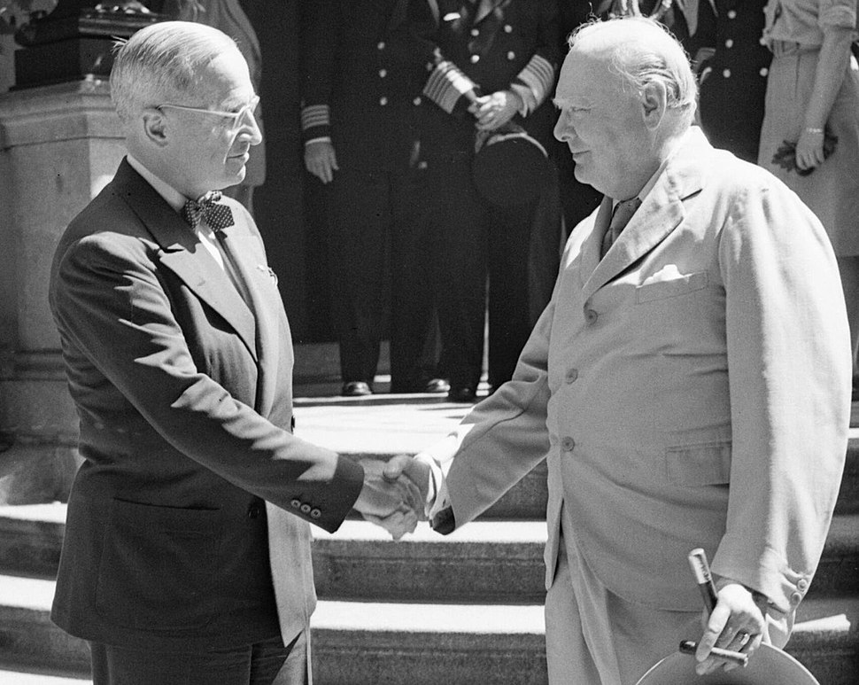 President Harry Truman and Winston Churchill shake hands on the steps of Truman's residence during the Potsdam conference, 16 July 1945. BU8944 (cropped)