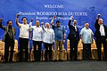 President Rodrigo Duterte and his delegates raise their fists before the members of the Filipino community in Brunei Darussalam at the indoor stadium of Hassanal Bolkiah National Sports Complex.jpg