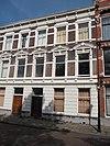 foto van Herenhuis in neo-renaissance trant, met in pleister gebosseerde parterre en in de verdieping vensters met gebogen frontons. Kroonlijst met consoles