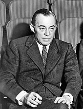 Photo of Rodgers, in middle age, seated in a theatre, wearing a suit, and holding a cigarette