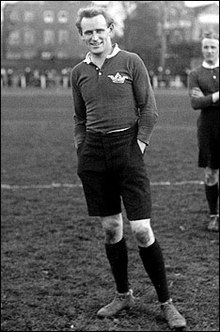 Black and white photograph of Poulton in 1911. He is standing on a rugby field, wearing rugby sports clothing and smiling and looking into the camera.