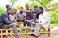 Rwandan old Man playing Igisoro with kids around.jpg