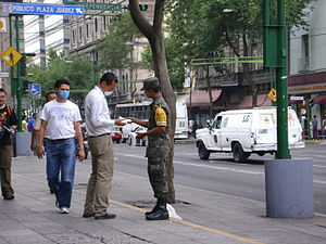 Mexican Armed Forces - A Mexican soldier wearing the identification of Plan DN-III-E, hands out protective mask to citizens during the 2009 flu pandemic.