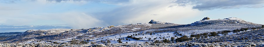 Dartmoor in winter covered in snow. Several tors top the sparsely vegetated hills.