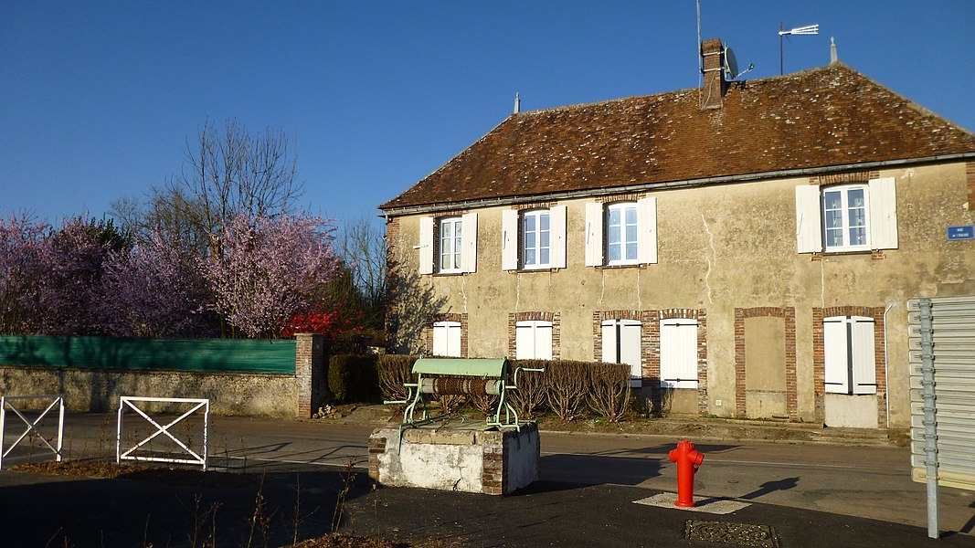 Saint-Loup-d'Ordon, Yonne, Burgundy, France.  Village well in front of the mairie. Saint-Loup church in the background.