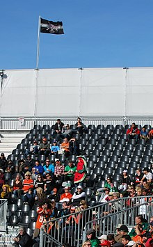 Fans seated in the stadium with one dressed as a giant watermelon slice