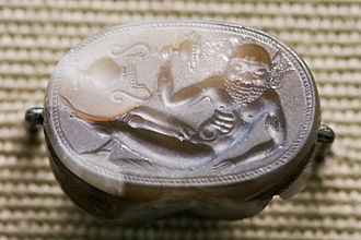 "Engraved gem - Reclining satyr, Etruscan c. 550 BC, 2.2 cm wide. Note the vase shown ""sideways""; it is characteristic of early gems that not all elements in the design are read from the same direction of view."