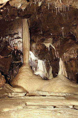 Potholler standing by pillar in limestone cave