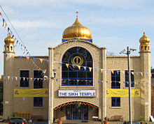 "A large symmetrical two-storey building of yellow brick. The centre bay, incorporating the entrance, juts out, it has a large window with a semicircular top on the first floor and above is a golden onion dome on a blue base. At the ends of the frontage are hexagonal pilasters with small octagonal windowed pavilions and onion domes on top. Above the entrance is a white sign saying ""The Sikh Temple"" in blue. Each side has one two-storey and one one-storey window, and also yellow banners alongside the Temple's name, on each side of the entrance is a wooden seat, and strings of bunting are stretched across the scene."