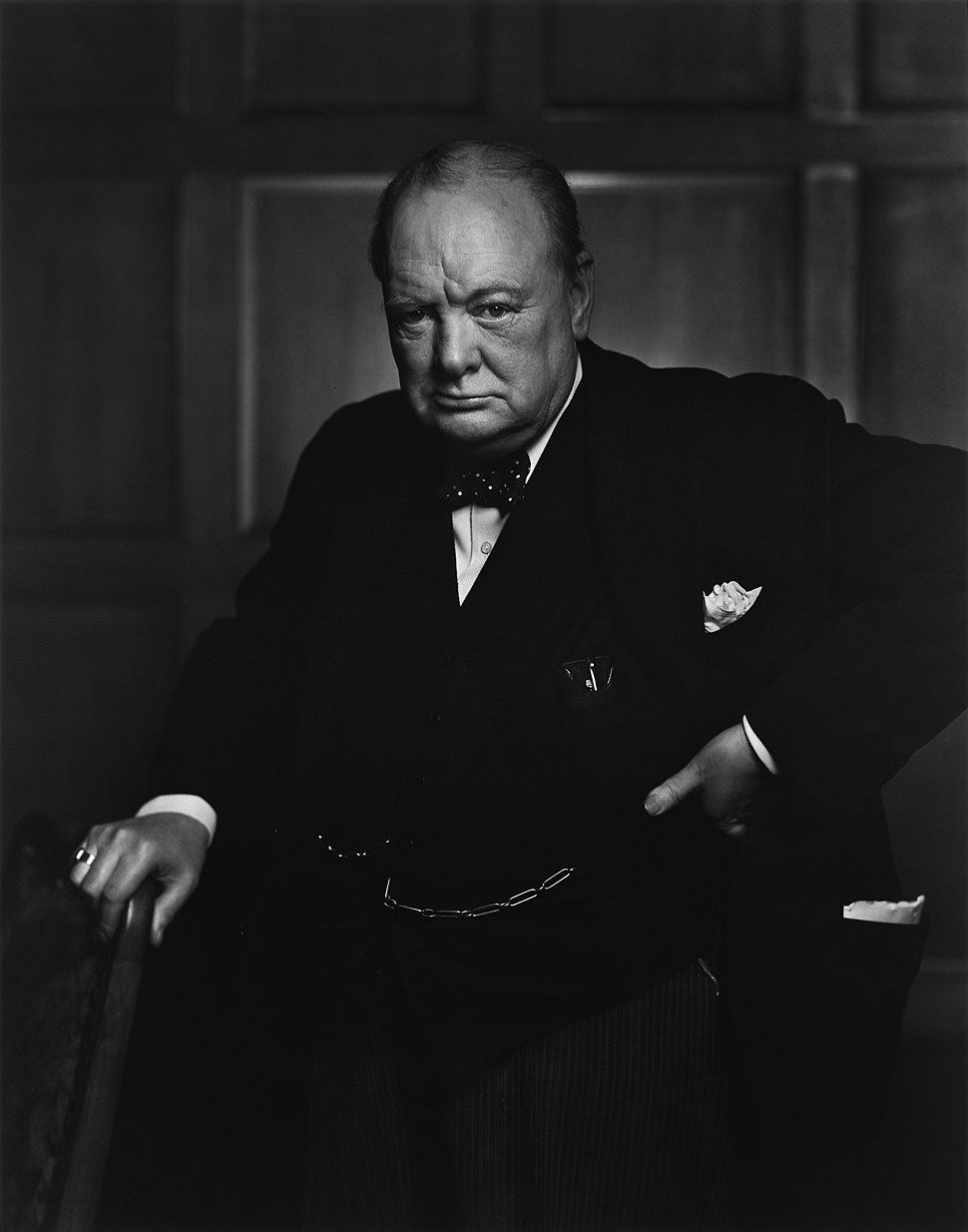 Churchill wearing a suit, standing and holding a chair