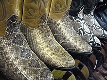 Five pairs of cowboy boots in a row facing half-right, all having snake-skin uppers. The first three pairs have uppers of gray and tan scales and ankle pieces of ecru colour. The last two pairs have uppers with prominent black and white diamond shaped scale patterns and navy blue ankles.