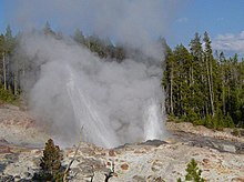 Steam shooting from ashen rocks with fir trees in the background.