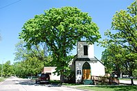 A single-storey white stucco church with a large elm tree spreading overhead.