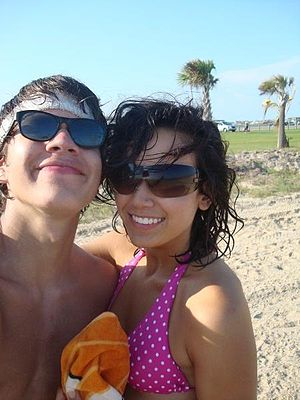 English: Two young people at beach smiling and...