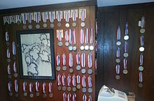 A wood-paneled room with many medals and a drawing of a grapevine hanging on the wall, and a cash register at the bottom.