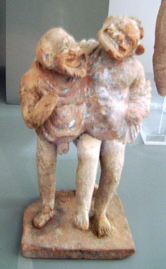 Fabula palliata - Terra cotta representation of two comic actors wearing masks with pallia slung over their shoulders