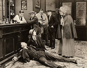 Raymond Bloomer - Beaten senseless in an underworld bar, Raymond Bloomer is aided by Marion Davies in a scene still from the 1919 silent drama The Belle of New York.