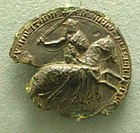Partly ruined black seal, showing Edward III on horseback, in armour and sword raised.