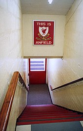 steps leading down to tunnel, above the tunnel is a sign with This Is Anfield in white letters on a red background, with a crest on it