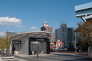 Toyosu Station - Exit 7 of the Tokyo Metro station in September 2011, with the end of the elevated Yurikamome tracks just visible