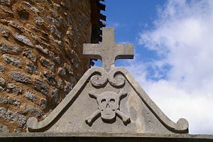 Rennes-le-Château - A Pediment decorated with a Memento mori Skull and crossbones figure above the entrance to the churchyard