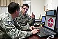 U.S. Air Force Senior Airman Daniel Burkhardt, right, and Staff Sgt. Christopher Bevins, both broadcast journalists supporting Joint Task Force-National Capital Region, put the finishing touches on a cell phone 130116-A-MZ229-004.jpg