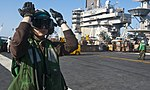 U.S. Navy Aviation Maintenance Administrationman Airman Anastasia Brown directs an MH-60S Knighthawk, not pictured, assigned to Helicopter Sea Combat Squadron (HSC) 8 on the flight deck of the aircraft carrier 121025-N-OY799-260.jpg