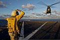 U.S. Navy Boatswain's Mate 2nd Class Cassandra Collier signals to a French Army SA 380 Puma helicopter as it lands aboard the amphibious dock landing ship USS Pearl Harbor (LSD 52) while underway in the Pacific 130628-N-WD757-359.jpg