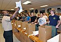 U.S. Navy Ship's Serviceman 1st Class Jermaine Johnson, left, a recruit division commander, instructs male recruits being issued new Navy equipment, clothing and toiletries inside the Golden 13 Recruit 121120-N-IK959-700.jpg
